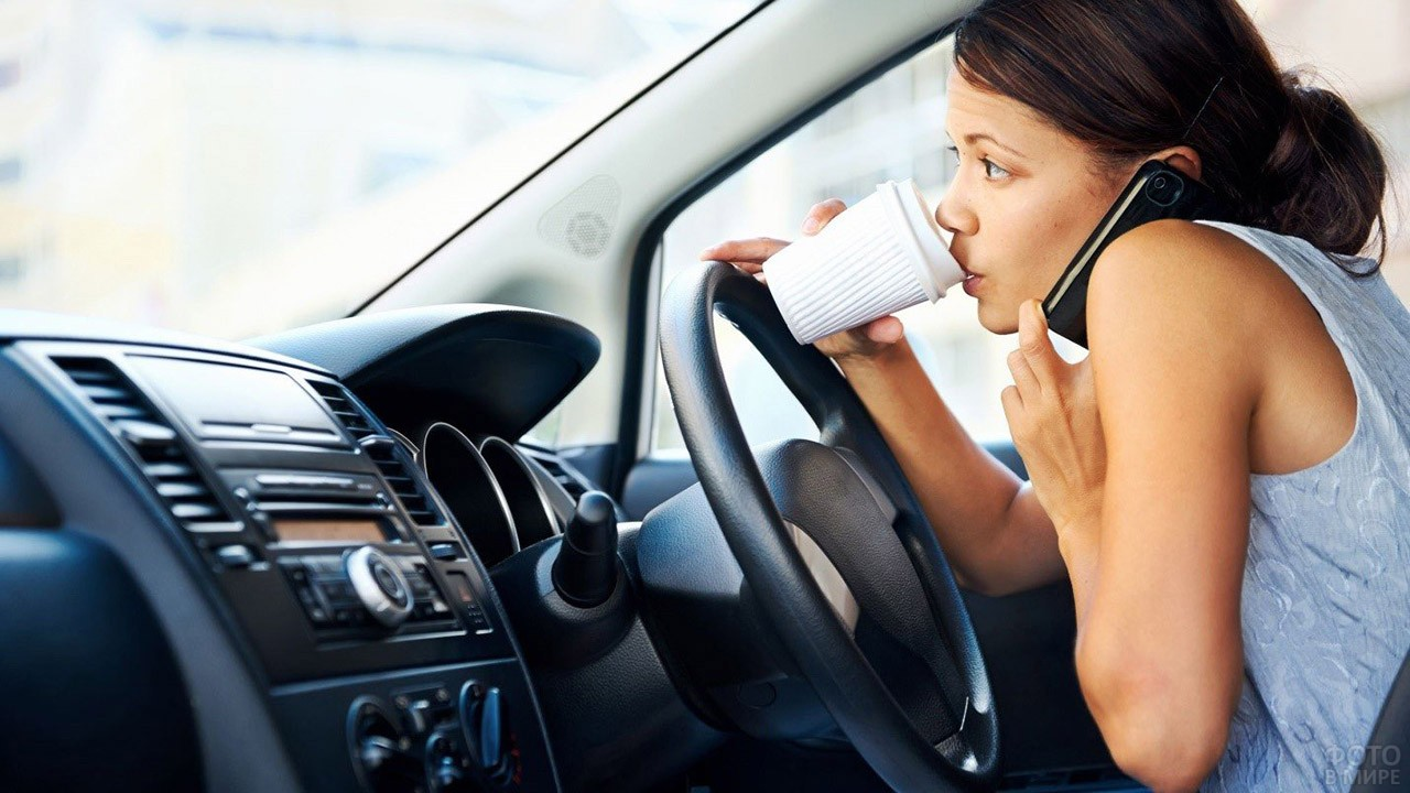 Автолюбительница говорит по телефону и пьёт кофе за рулём