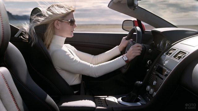 Блондинка мчится за рулём Астон Мартин