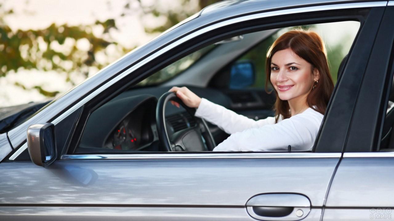 Девушка улыбается с водительского сиденья
