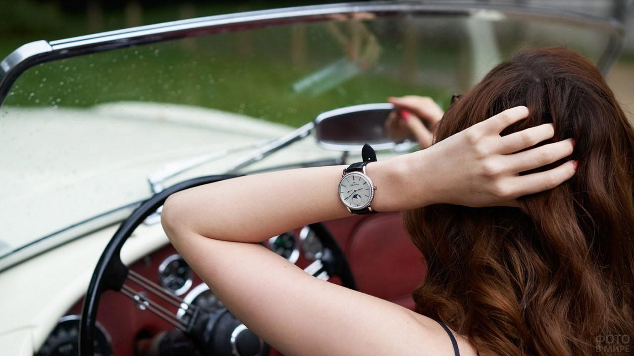 Девушка за рулём кабриолета поправляет причёску