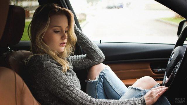 Юная барышня в рваных джинсах за рулём авто