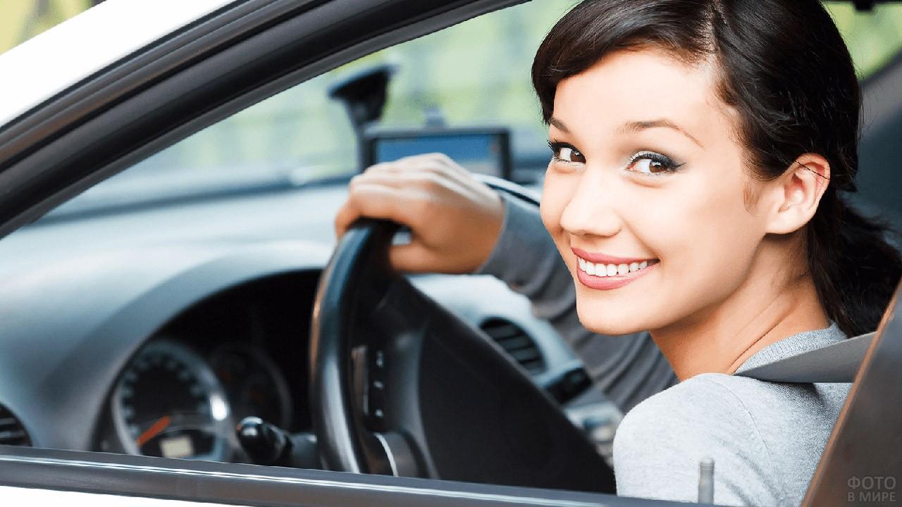 Юная брюнетка выглядывает в окно автомобиля