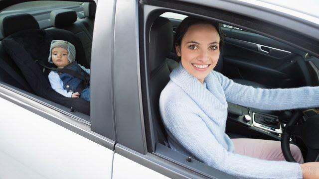 Мамочка-автолюбительница улыбается в окно