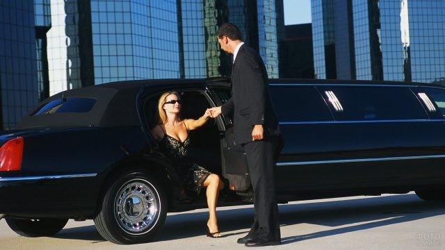 Мужчина помогает даме выйти из лимузина