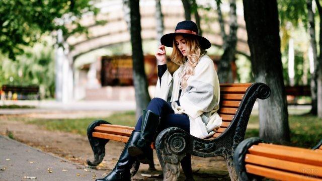 Барышня в шляпе сидит на парковой скамейке