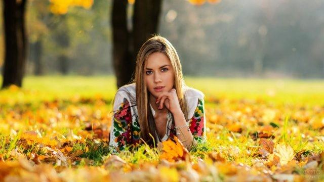 Блондинка лежит на усыпанном осенними листьями газоне