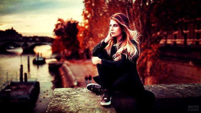Блондинка сидит на парковой набережной