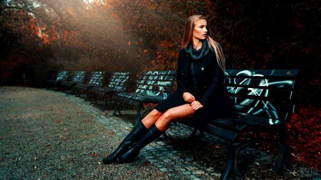 Блондинка в чёрном на парковой аллее с граффити на скамейках