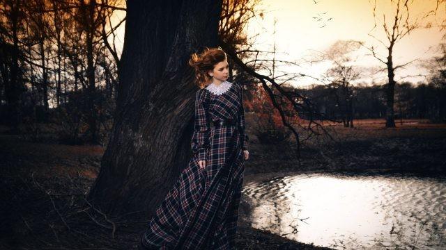 Девочка в шотландском платье в ненастную погоду в парке