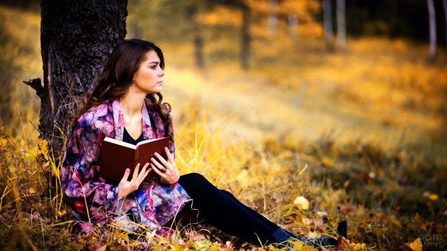 Девушка с книгой под осенним деревом