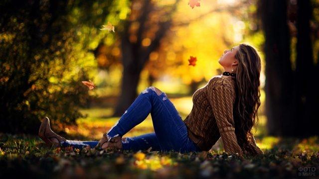Девушка сидит в парке под листопадом