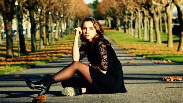 Девушка в чёрном платье сидит на осенней аллее