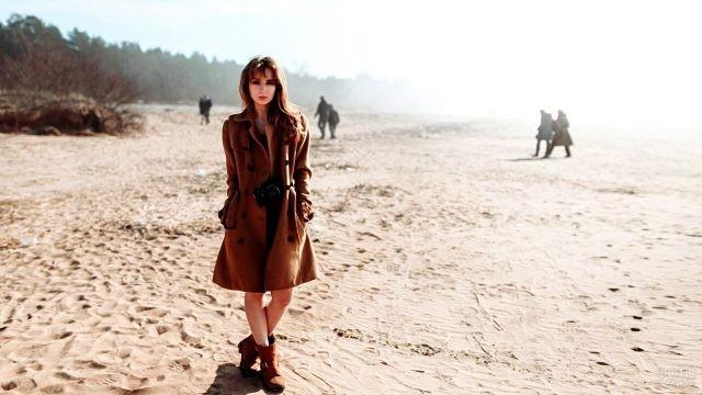 Девушка в плаще с фотоаппаратом на песчаном пляже