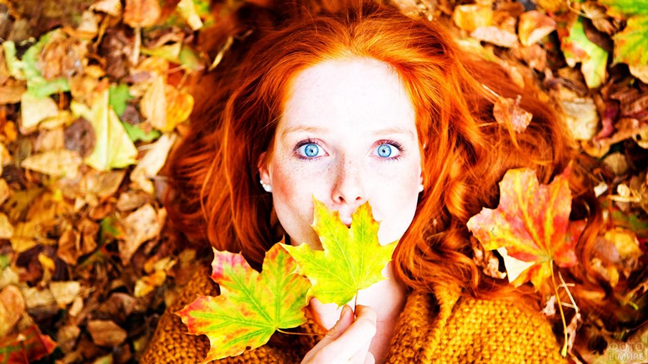 Голубоглазая рыжеволосая девушка среди осенних листьев