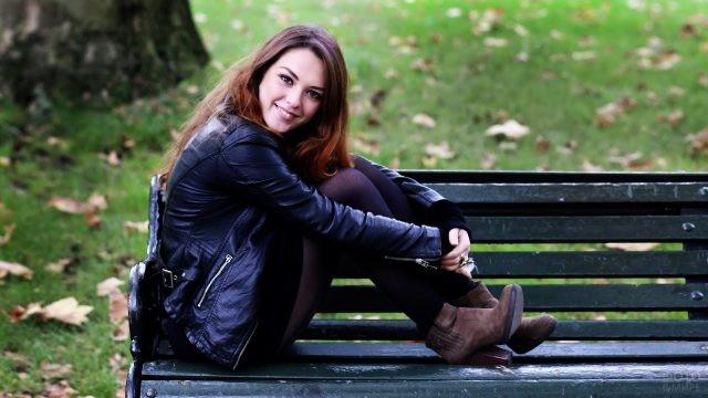 Хорошенькая шатенка на скамейке в осеннем парке