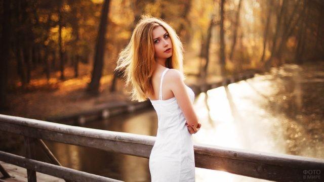 Юная красавица на мосту в осеннем парке