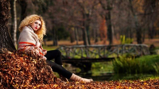 Кудрявая девушка сидит под деревом в осеннем парке