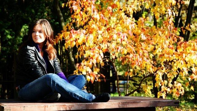 Миловидная девушка в кожаной куртке сидит в позе йоги