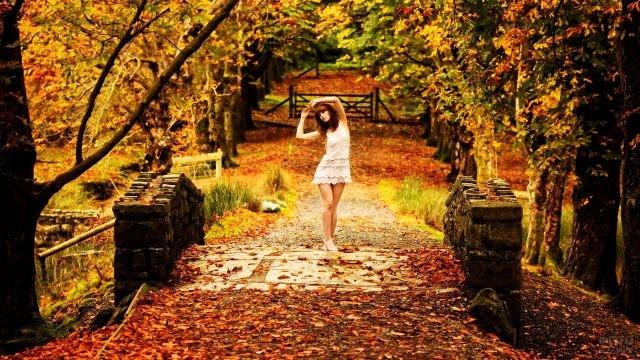 Рыжеволосая девушка в белом платьице среди листопада в парке
