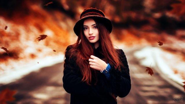Шатенка в шляпке стоит под листопадом