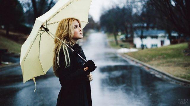 Светловолосая девушка под зонтом посреди улицы