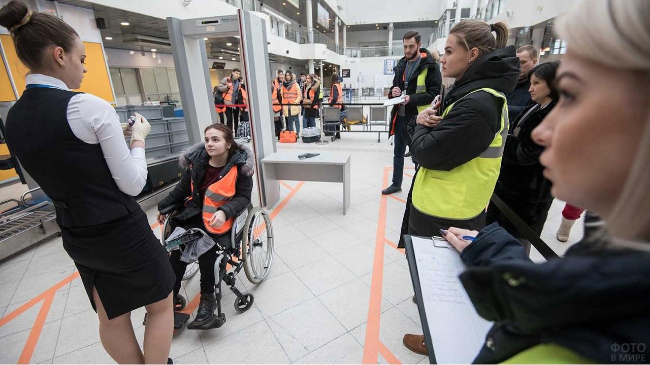 Сотрудники аэропорта встречают пассажирку в инвалидном кресле