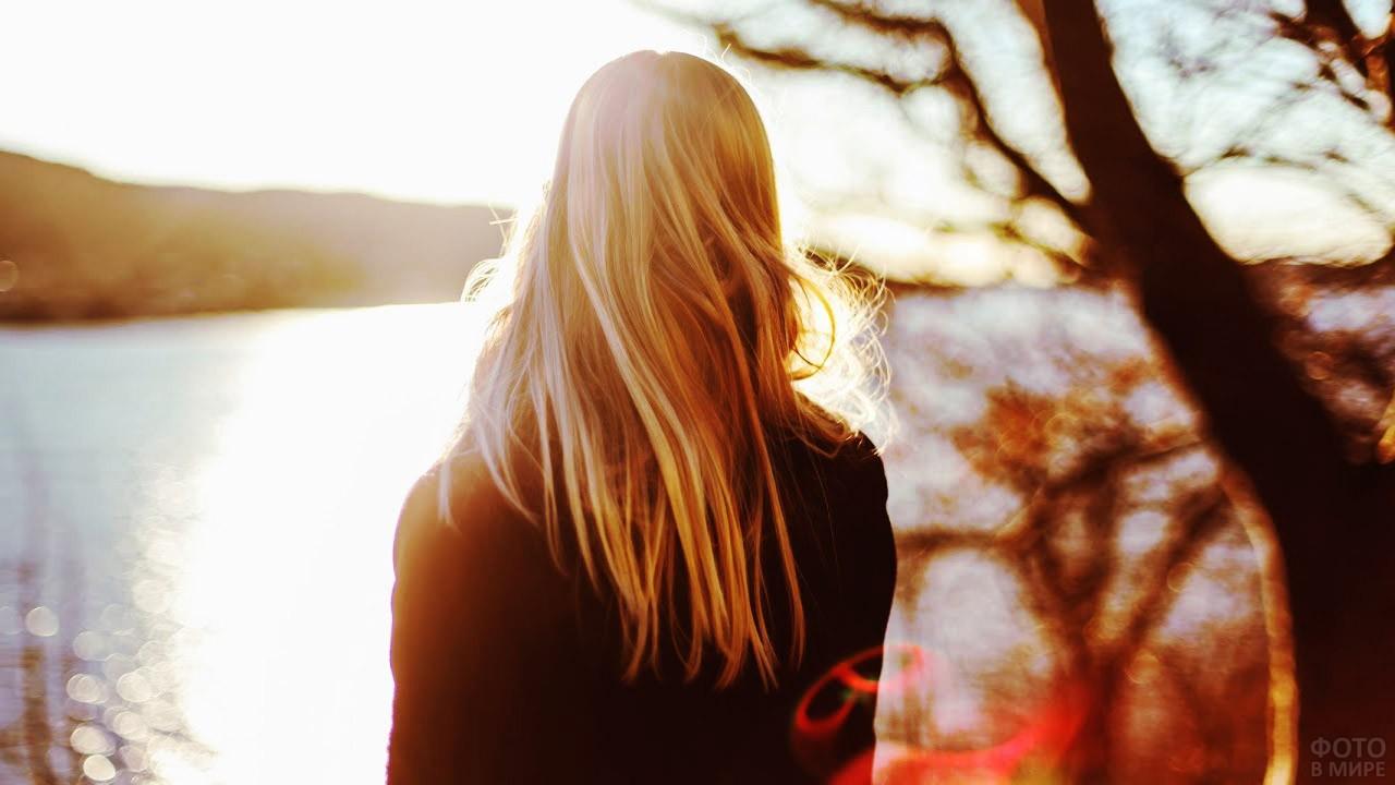 Блондинка смотрит на озеро