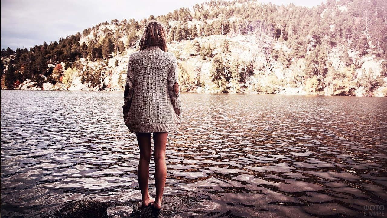Блондинка в вязаной кофте на берегу реки