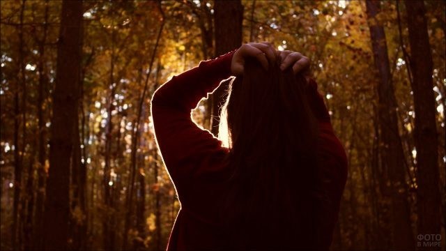 Брюнетка любуется осенним солнцем сквозь кроны леса