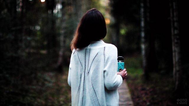 Брюнетка в белом свитере с термосом в руке