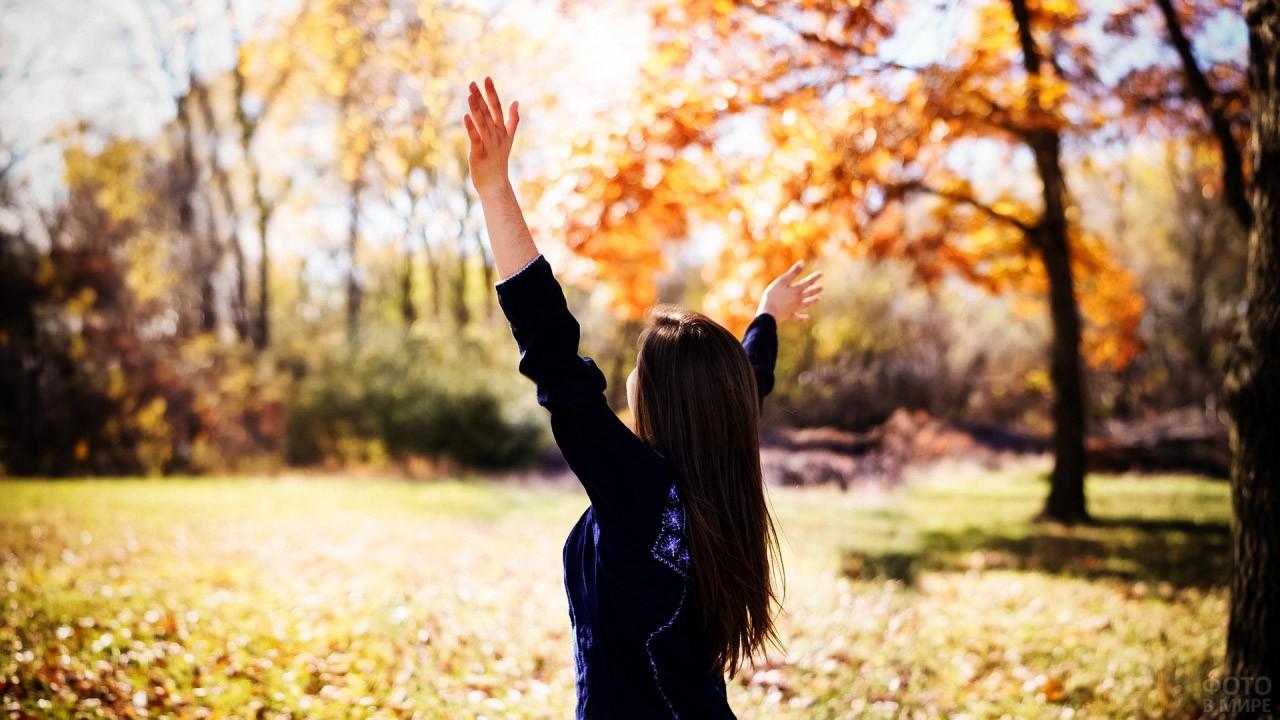 Брюнетка в осеннем парке подняла руки к солнцу