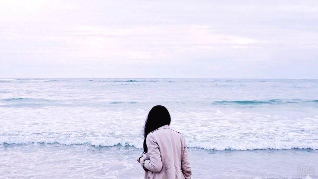 Брюнетка в плаще на берегу моря