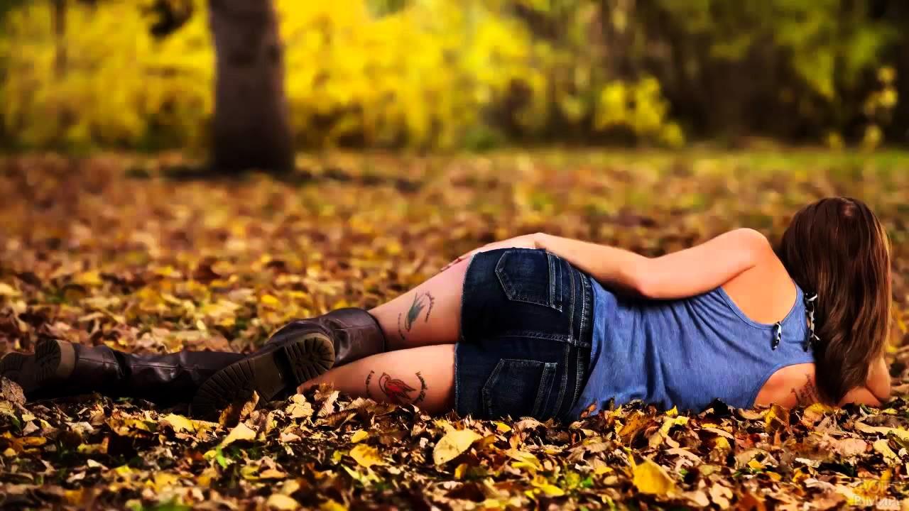 Дерзкая брюнетка лежит на опавшей листве в парке