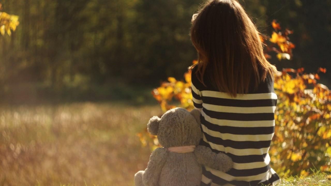 Девочка с плюшевым мишкой смотрят на осенний лес