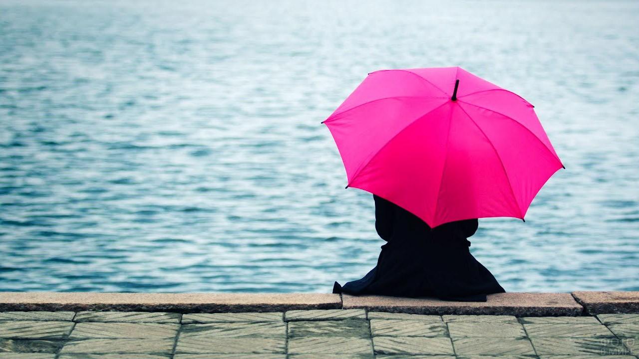 Девушка под розовым зонтом сидит на набережной