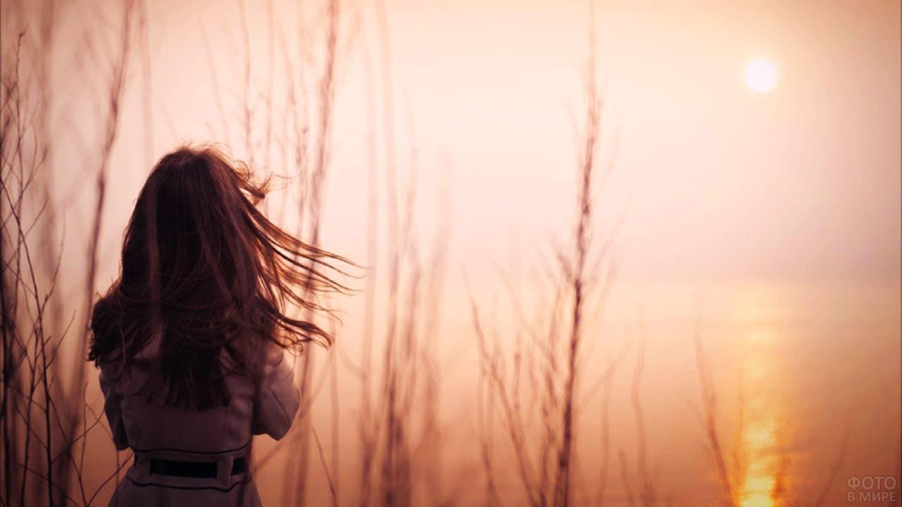 Девушка с развевающимися волосами на фоне восхода солнца