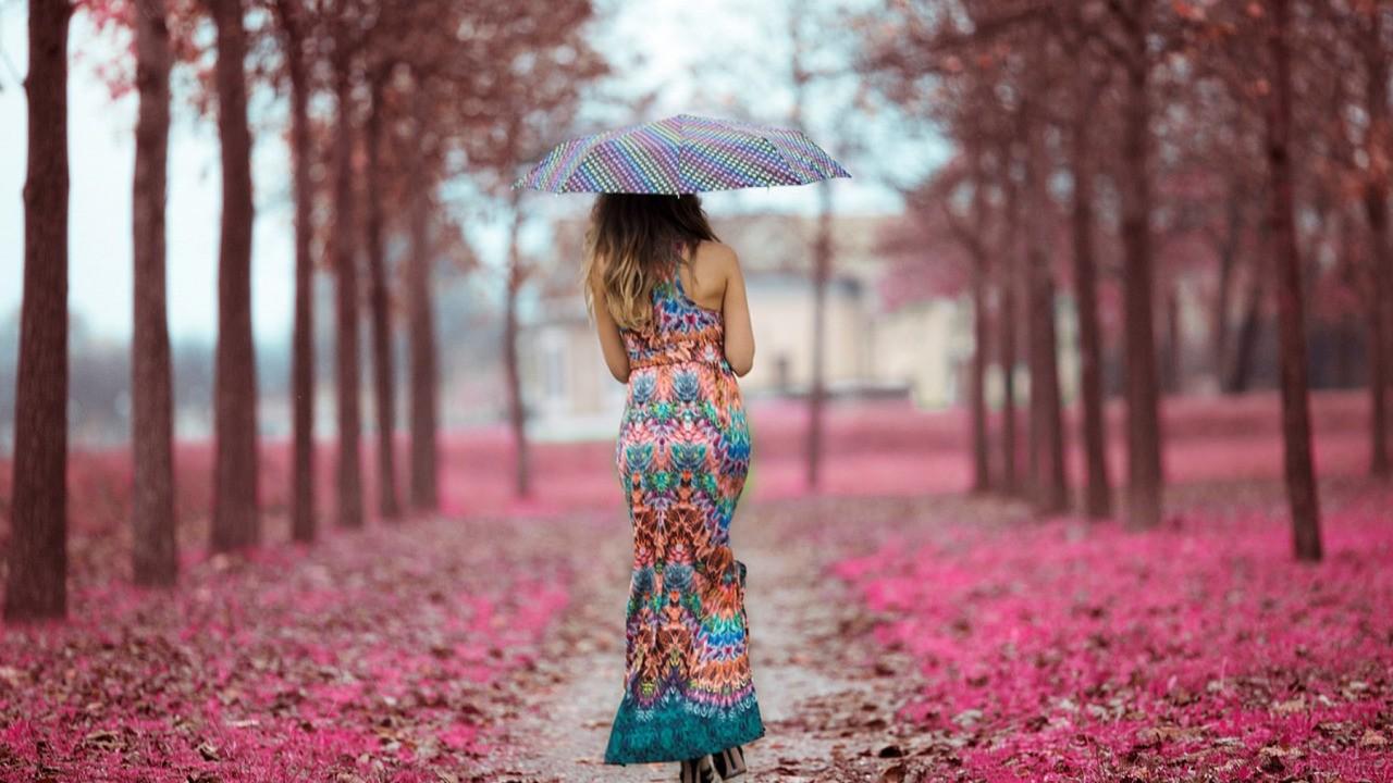 Девушка с зонтом идёт по парку