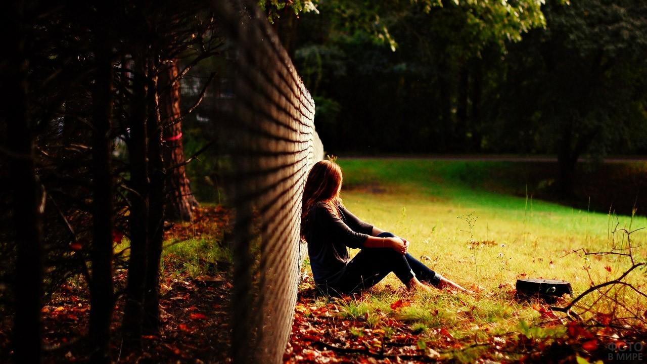 Девушка сидит у ограды в осеннем поле