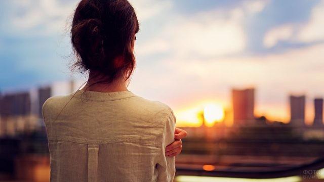 Девушка смотрит на закат над городом