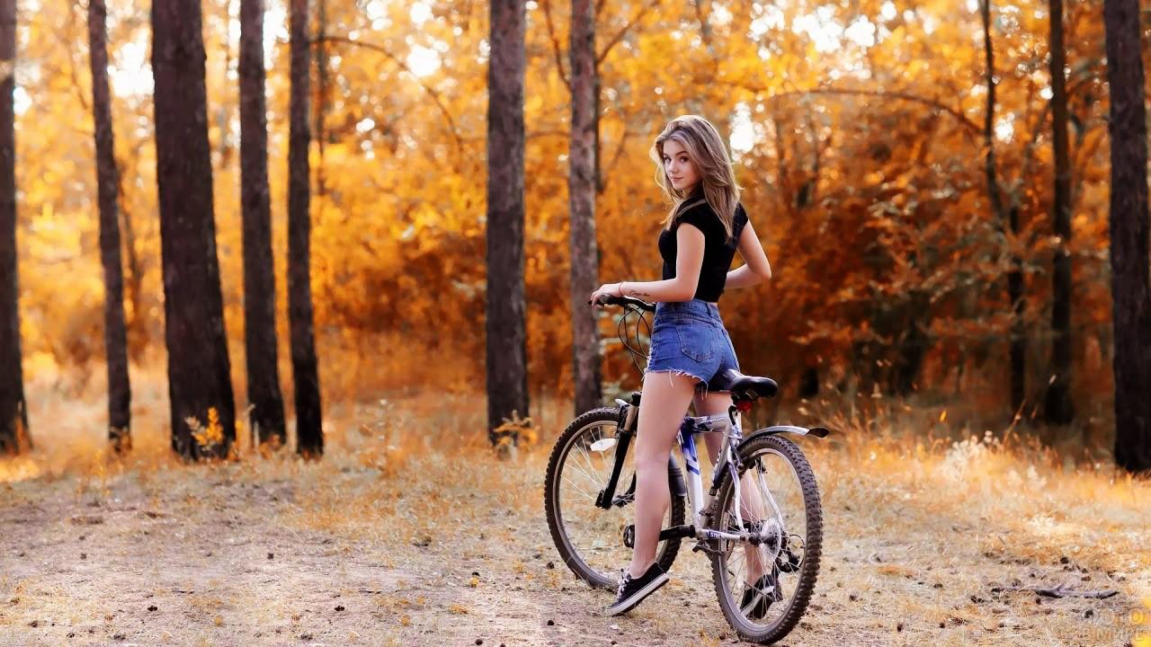 Хорошенькая велосипедистка в осеннем лесу