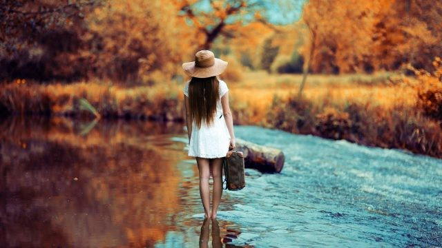 Худенькая барышня с чемоданом в руке стоит посреди ручья
