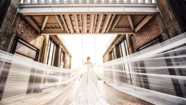 Невеста в платье с шлейфом на качелях