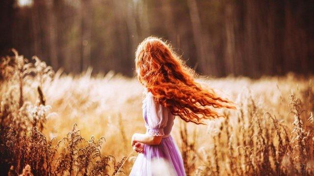 Рыжая девочка кружится в осеннем поле
