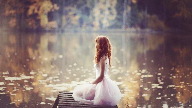 Рыжеволосая девочка в белом сидит у пруда