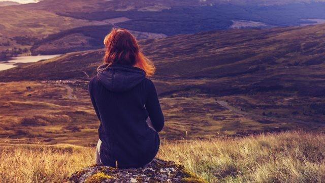 Рыжеволосая девушка смотрит на долину с вершины холма
