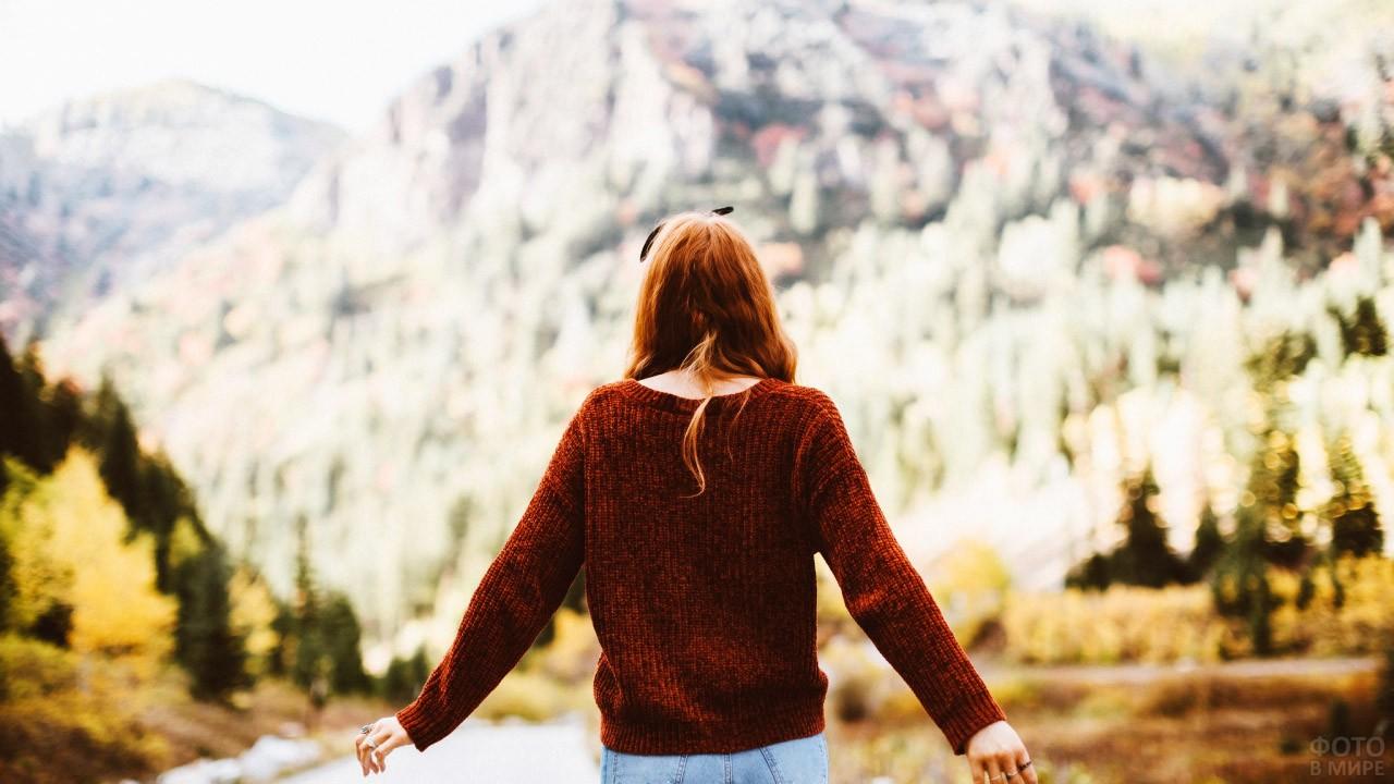 Рыжеволосая девушка смотрит на горы