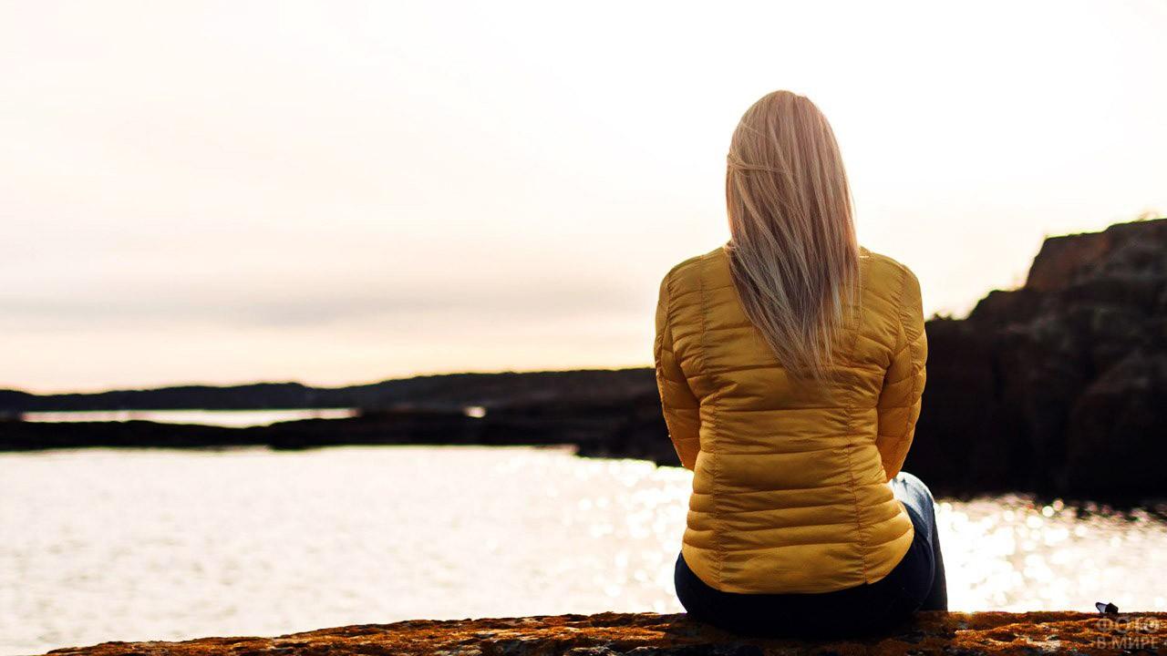 Светловолосая девушка смотрит на озеро