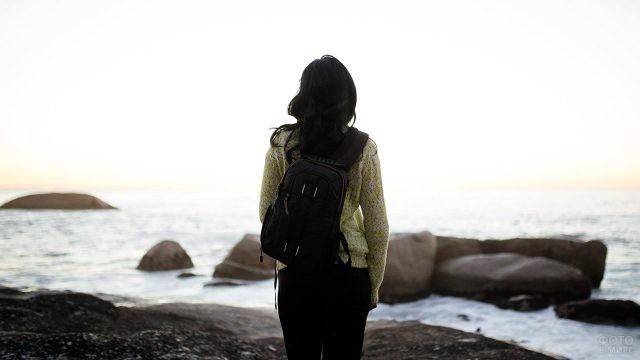 Туристка с рюкзачком стоит на берегу моря