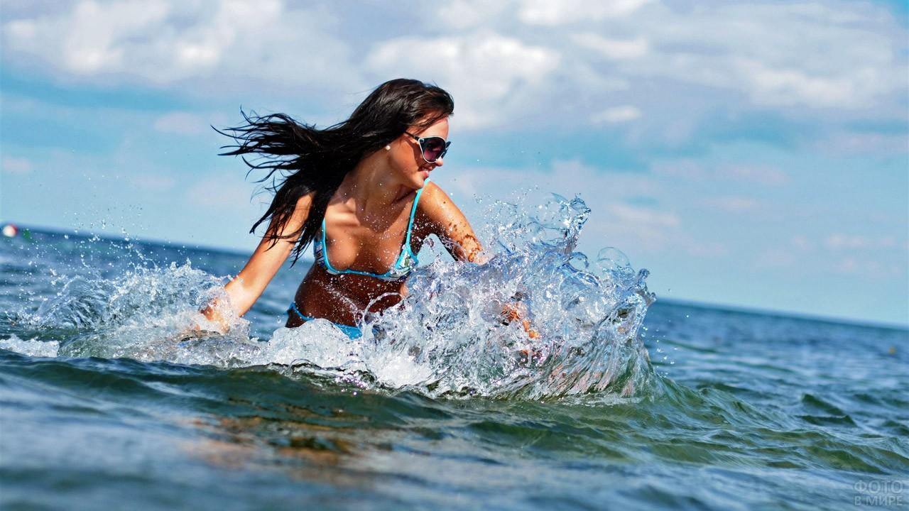 Брюнетка в голубом бикини плещется в море