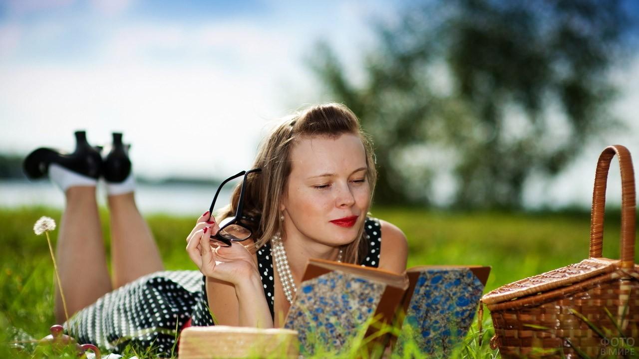 Дачница в ретро-наряде читает книжку лёжа на траве